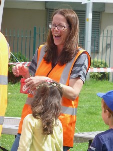 Emma in dago orange hi vis laughing as she tries to get lid off raffle tin