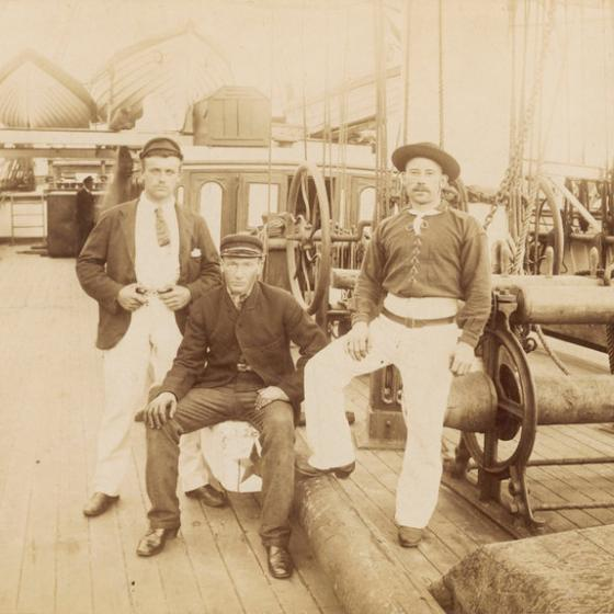 Three working men sitting on luggage on a deck, with straw hats and white trousers