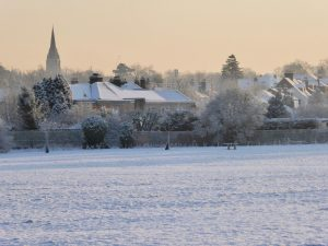 frosty field with houses and spire behind