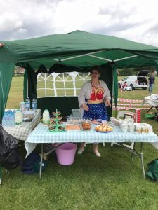 lady with superwoman apron in gazebo with cakes