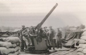 WW2 artillery men around large gun