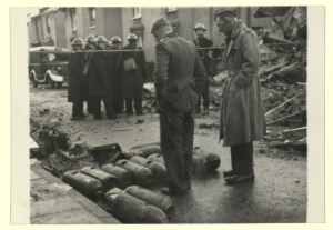 men looking at bombs laid at the side of the road